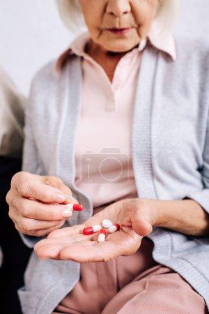 Ausgeschnittener Blick auf Seniorin, die auf Sofa sitzt und Tabletten in Wohnung hält