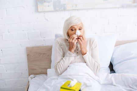 Foto de Enferma anciana que estornuda y mantiene a sus parientes en la cama - Imagen libre de derechos
