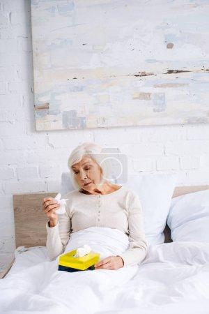 Photo pour Séduisante et malade femme âgée tenant la serviette au lit - image libre de droit