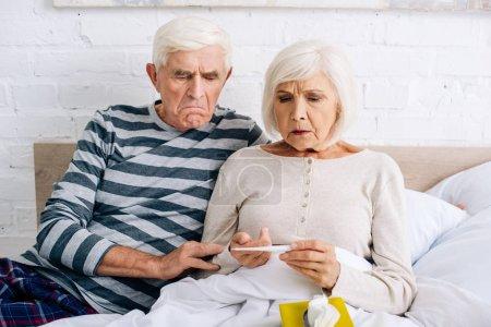 Photo pour Triste mari et femme regardant un thermomètre dans un appartement - image libre de droit