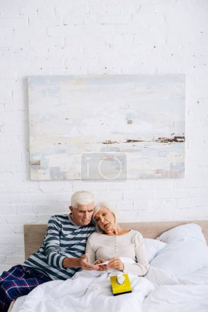 Photo for Handsome husband and wife looking at thermometer in apartment - Royalty Free Image