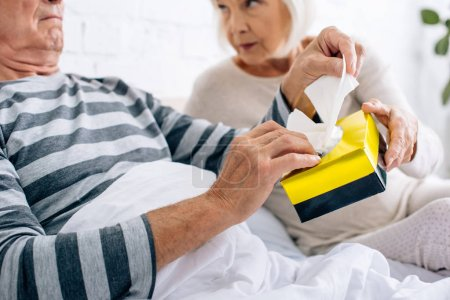 Photo for Cropped view of wife giving napkins to ill husband in bed - Royalty Free Image