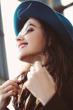 Photo pour Heureuse fille élégante posant dans les lunettes et le chapeau sur le toit urbain - image libre de droit