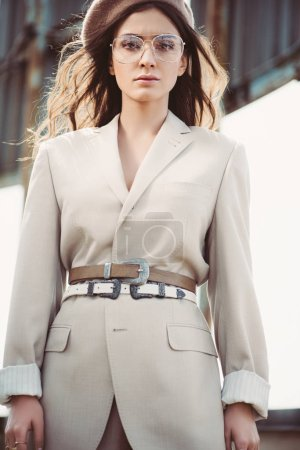 attractive fashionable woman posing in beige suit and beret on roof