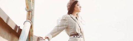 Photo for Elegant fashionable woman posing in beige suit and beret on roof - Royalty Free Image