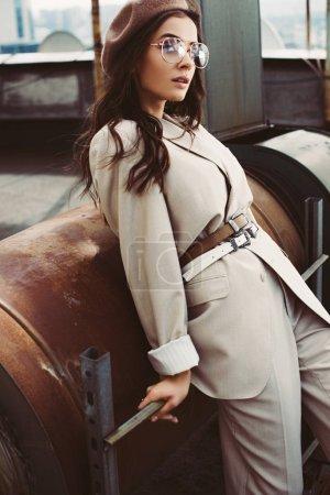 Photo pour Attrayant fille à la mode posant en costume beige et béret sur le toit urbain - image libre de droit