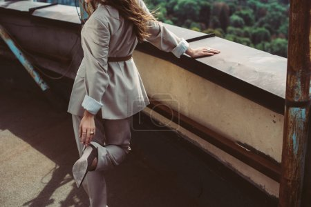 Photo for Cropped view of elegant trendy woman posing in beige suit on urban roof - Royalty Free Image