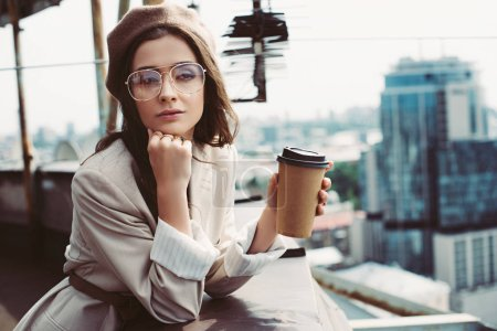 Photo for Elegant pensive girl in beige suit and beret posing on roof with coffee to go - Royalty Free Image