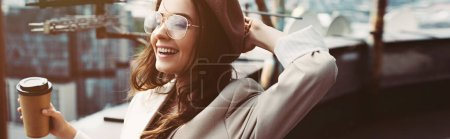 Photo for Smiling fashionable girl in beige suit and beret posing on roof with coffee to go - Royalty Free Image