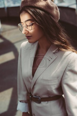 Photo for Stylish girl with closed eyes posing in beige suit and beret on urban roof - Royalty Free Image
