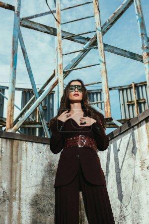 modèle attrayant posant en costume bordeaux tendance sur le toit urbain