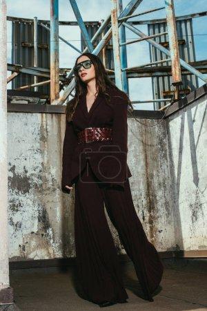 Photo pour Beau modèle posant en costume bordeaux tendance sur le toit urbain - image libre de droit