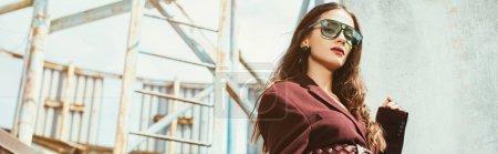 Photo pour Beau modèle élégant posant en tenue bourguignonne à la mode sur un toit urbain - image libre de droit