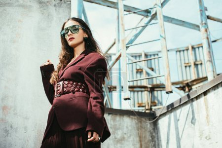 Photo for Stylish model posing in trendy burgundy suit and sunglasses on urban roof - Royalty Free Image