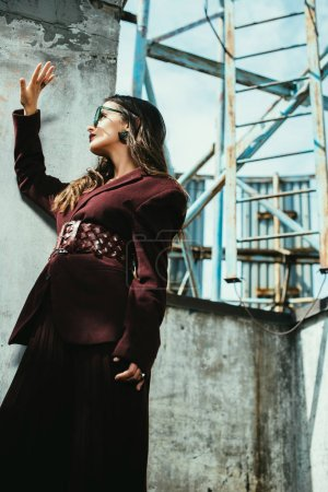 Foto de Mujer de moda con traje de fuego y gafas de sol a la moda en el techo urbano. - Imagen libre de derechos