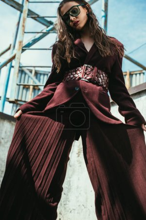 Photo for Elegant model posing in trendy burgundy suit and sunglasses on urban roof - Royalty Free Image