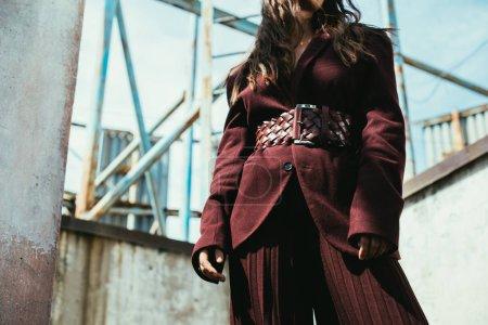 Photo pour Crochet vue d'une élégante fille posant en tenue bourguignonne à la mode sur un toit urbain - image libre de droit
