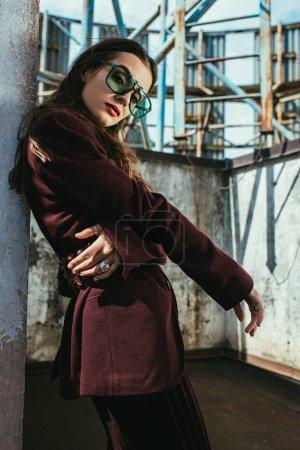 Photo pour À la mode posant en combinaison bourgogne tendance et lunettes de soleil sur le toit urbain - image libre de droit