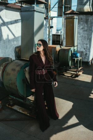 Photo for Stylish elegant woman posing in trendy burgundy suit and sunglasses on urban roof - Royalty Free Image