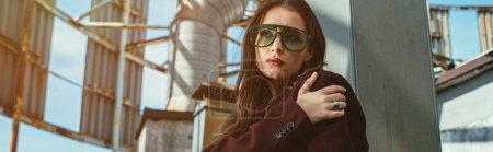 Photo pour Élégante femme à la mode posant en combinaison bourgogne à la mode et lunettes de soleil sur le toit urbain - image libre de droit
