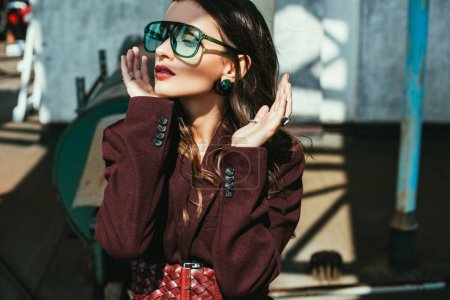 Photo for Fashionable girl posing in trendy burgundy suit and sunglasses on urban roof - Royalty Free Image