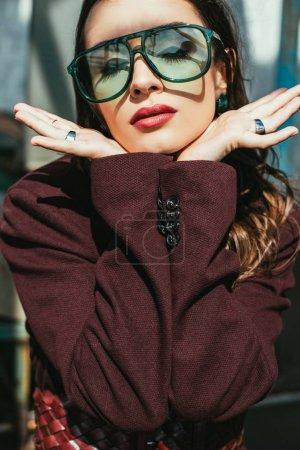 Photo pour Femme élégante posant en costume bordeaux tendance et lunettes de soleil sur le toit urbain - image libre de droit