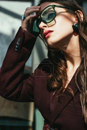 Photo pour Femme à la mode posant en costume bordeaux tendance et lunettes de soleil sur le toit urbain - image libre de droit