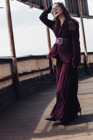 Photo pour Femme élégante posant en combinaison bourgogne tendance et lunettes de soleil sur le toit urbain - image libre de droit