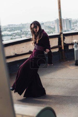 Photo pour Jolie femme élégante posant en combinaison bourgogne tendance et lunettes de soleil sur le toit urbain - image libre de droit