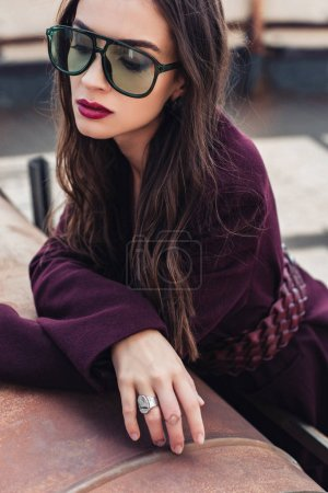 Photo for Attractive elegant girl posing in trendy burgundy suit and sunglasses on urban roof - Royalty Free Image