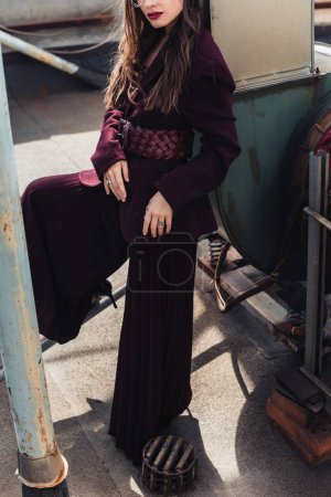 Photo for Cropped view of stylish girl posing in trendy burgundy suit on urban roof - Royalty Free Image