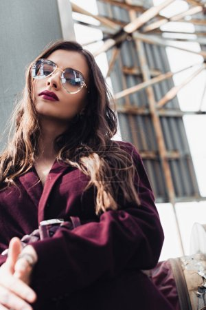 Photo for Beautiful girl posing in trendy burgundy suit and sunglasses on urban roof - Royalty Free Image