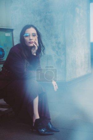 Photo pour Fille élégante à la mode posant en costume bordeaux à la mode et lunettes de soleil sur le toit urbain - image libre de droit