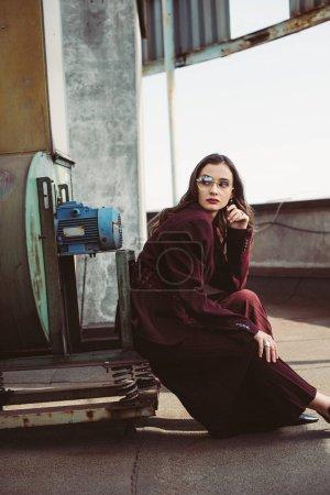 Photo pour Belle fille élégante posant en costume bordeaux tendance et lunettes de soleil sur le toit urbain - image libre de droit