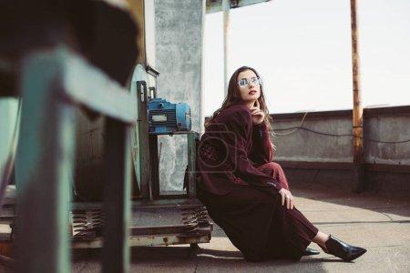 Photo pour Jolie et élégante fille posant en combinaison bourgogne tendance et lunettes de soleil sur le toit urbain - image libre de droit