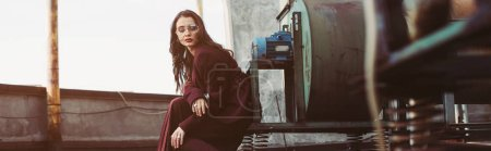 stylish elegant girl posing in trendy burgundy suit and sunglasses on urban roof