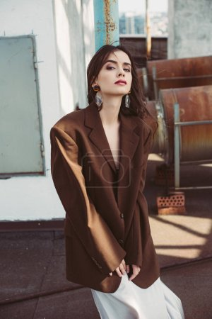 Photo for Beautiful stylish girl posing in silk dress and brown jacket on roof - Royalty Free Image