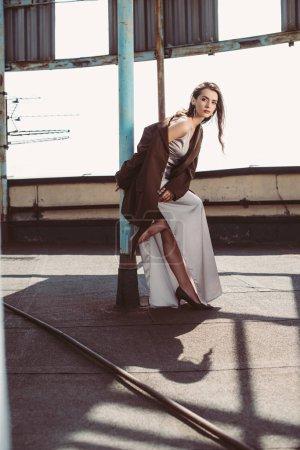 Photo pour Fille élégante à la mode posant en robe de soie et veste brune sur le toit - image libre de droit