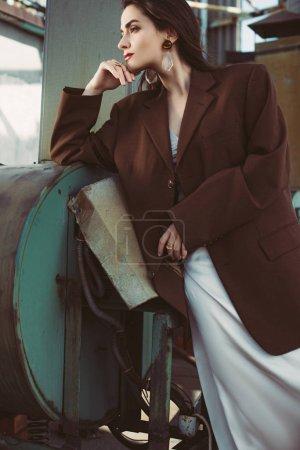 elegant beauty posing in silk dress and brown jacket on roof
