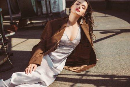 Foto de Atractiva mujer elegante con vestido de seda y chaqueta marrón en el techo - Imagen libre de derechos