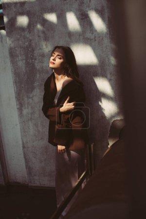 Foto de Hermoso modelo elegante que presenta vestido de seda y chaqueta marrón en el techo. - Imagen libre de derechos