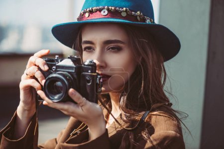 elegant woman in hat taking photos on retro photo camera on roof