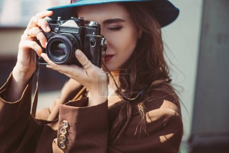 Photo for Attractive woman in hat taking photos on retro photo camera on roof - Royalty Free Image