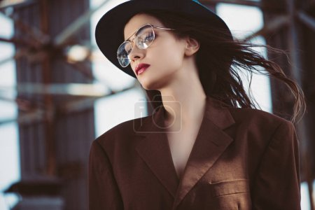 Photo for Stylish elegant woman posing in hat, eyeglasses and brown jacket on roof - Royalty Free Image