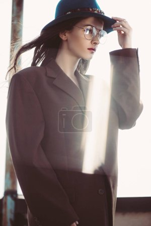 elegant fashionable woman posing in hat, eyeglasses and brown jacket on roof