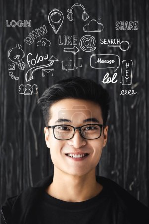 smiling asian man in glasses looking at camera on wooden background with illustration