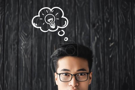 cropped view of asian man in glasses looking at camera on wooden background with idea illustration