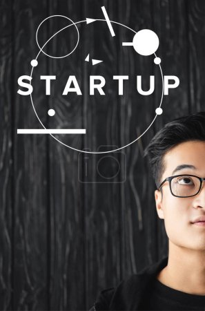 cropped view of asian man in glasses looking at illustration with startup lettering