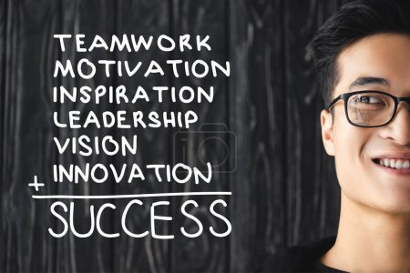 cropped view of smiling asian man in glasses and illustration with concept words of success