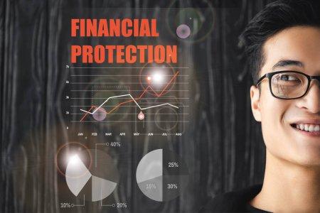 Photo pour Crochet vue d'un pirate asiatique souriant regardant une illustration avec un lettrage de protection financière - image libre de droit